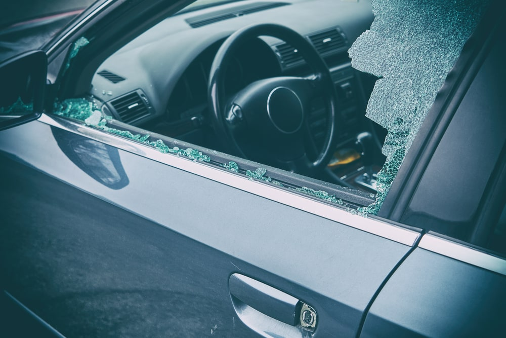 Driver side window repair. Car with shattered car door window on the driver side. Part of the window hangs in the door frame
