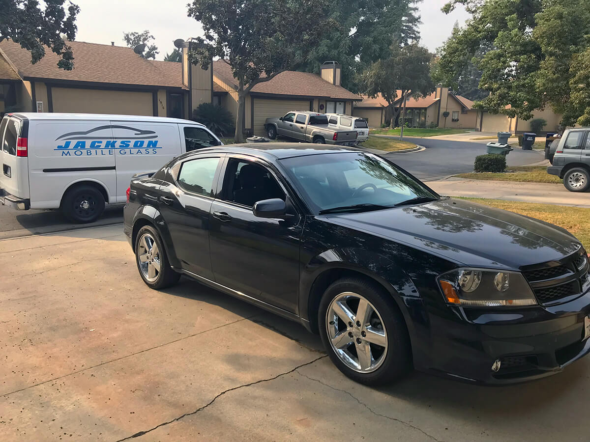 Black Dodge Avenger with new windshield replacement parked on driveway with the Jackson Mobile Glass repair van parked behind it