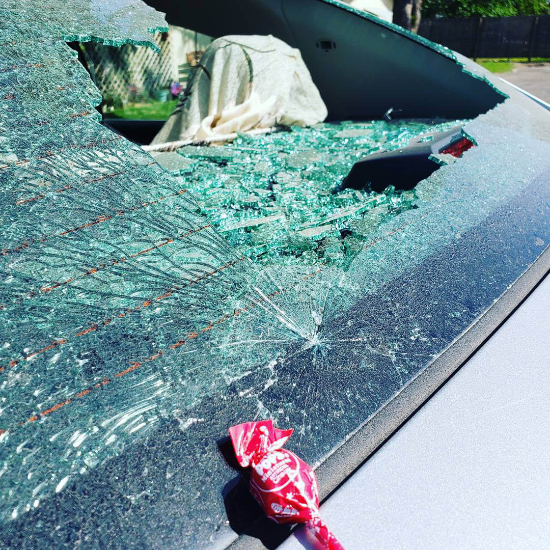 A shattered and partially busted out rear car window broken out by a lollipop with the red Tootsie Pop resting beneath it
