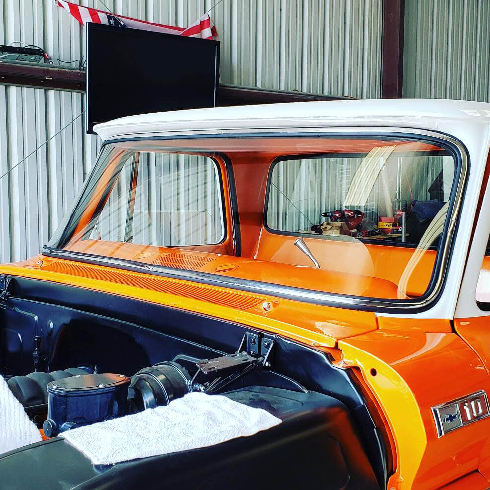 Orange classic Chevy truck with new windshield parked inside a corrugated metal garage