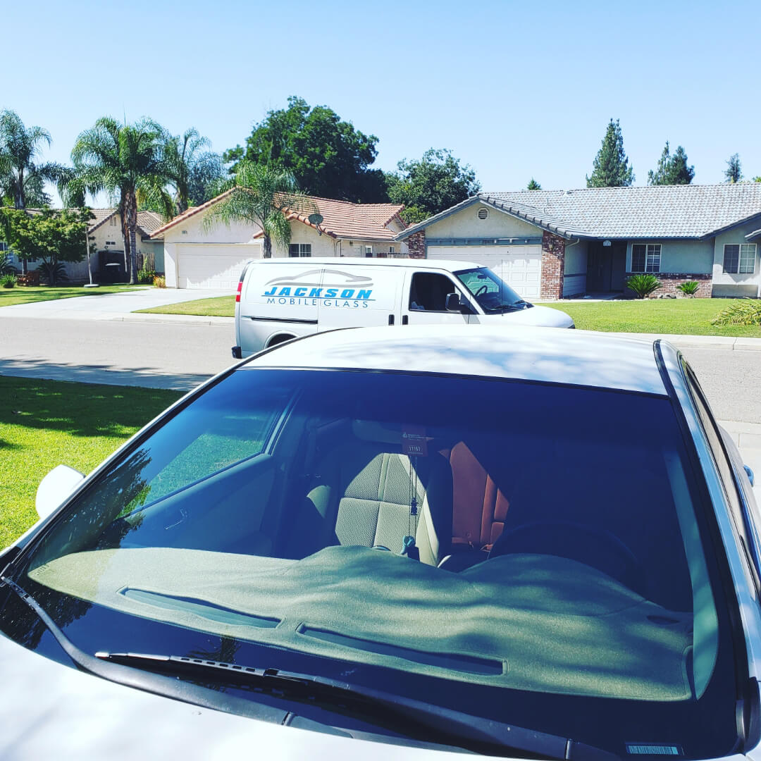 New car windshield replaced on customer's driveway with Jackson Mobile Glass repair van parked on the road