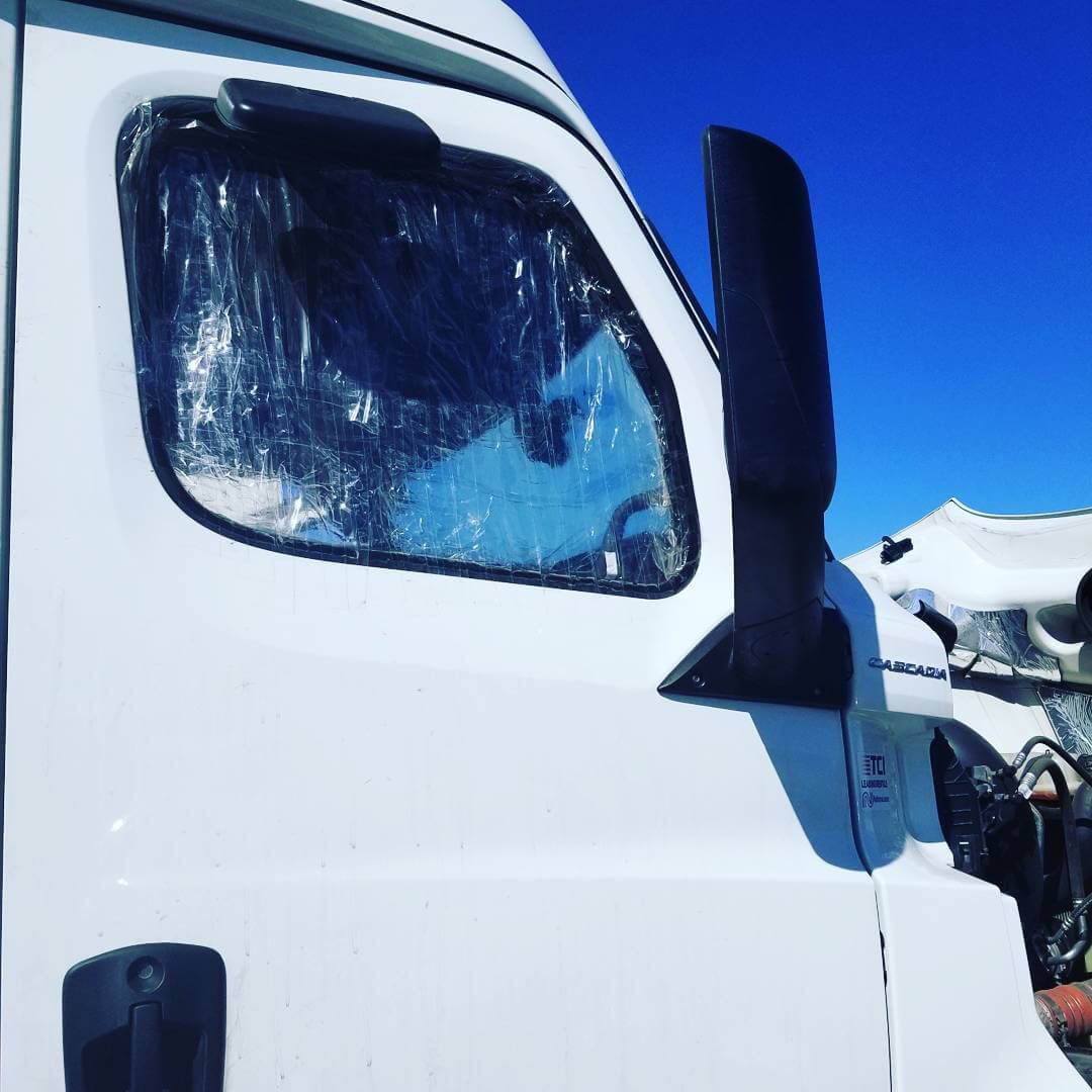 Broken front passenger window on a white semi truck held together with clear tape