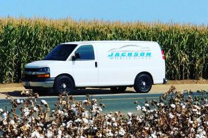 Auto glass repair. Jackson Mobile Glass utility van parked on the road between corn and cotton fields in Visalia, CA.
