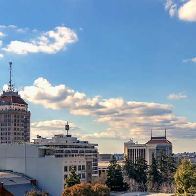 Fresno auto glass repair. Fresno skyline. Tall buildings tower over a park with large pine trees and decorate the blue sky.