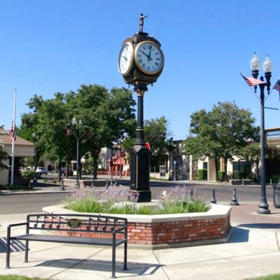 Porterville auto glass repair. Downtown Clock in the city of Porterville. Clock is old fashioned with a small bronze statue.
